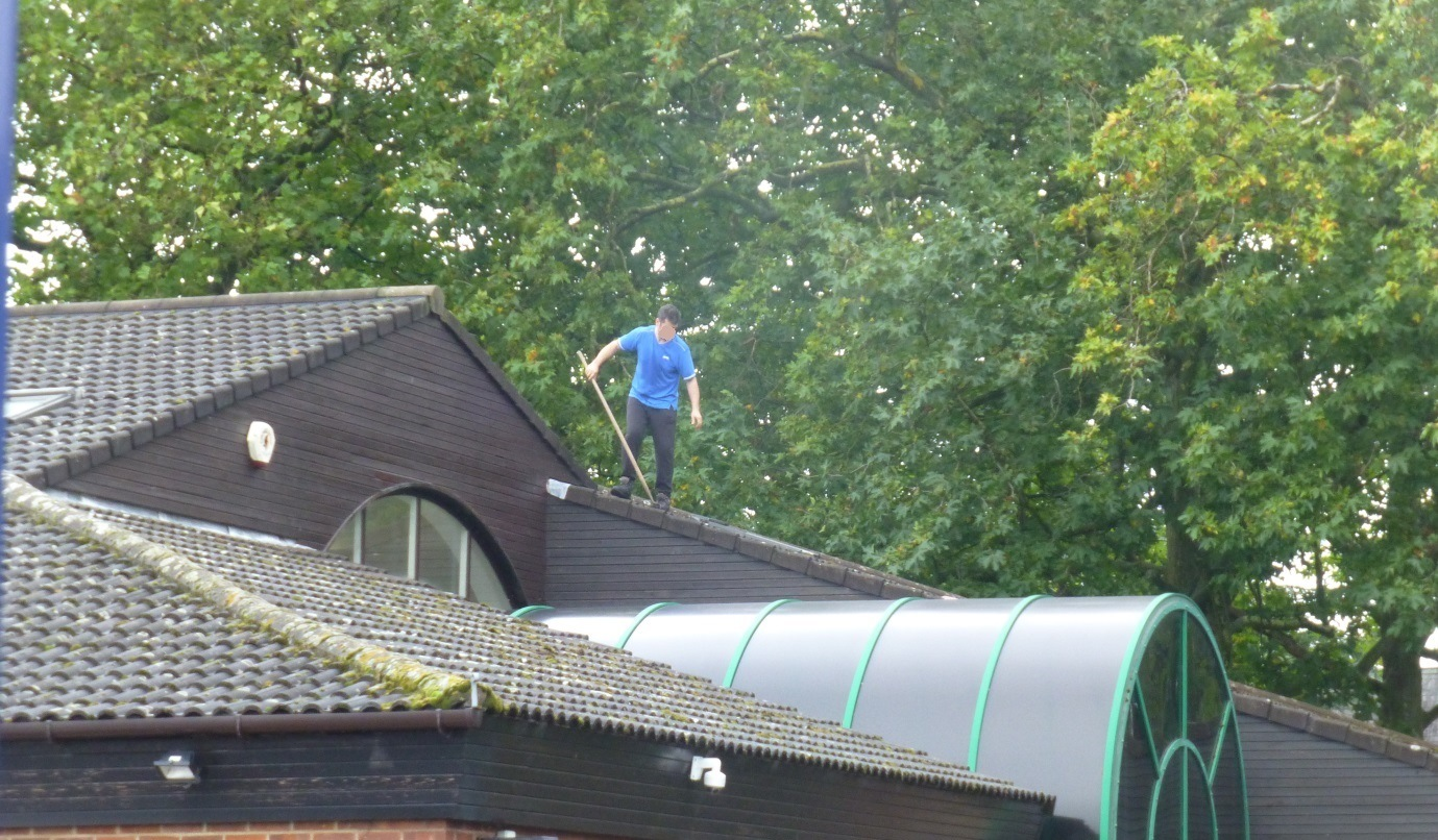 Photo 1 – Man working on roof protection from falling